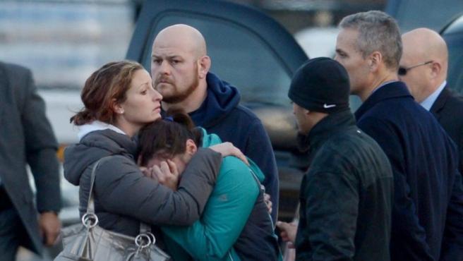 Varias personas reciben consuelo tras la masacre acontecida en la escuela primaria de Sandy Hook.