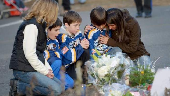 Varias personas se arrodillan junto a unas flores y velas colocadas junto a la escuela Sandy Hook, en Newtown, donde tuvo lugar la matanza perpetrada por Adam Lanza, un joven de 20 años.