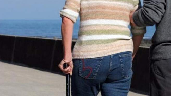 Una mujer con esclerosis, caminando con bastón.