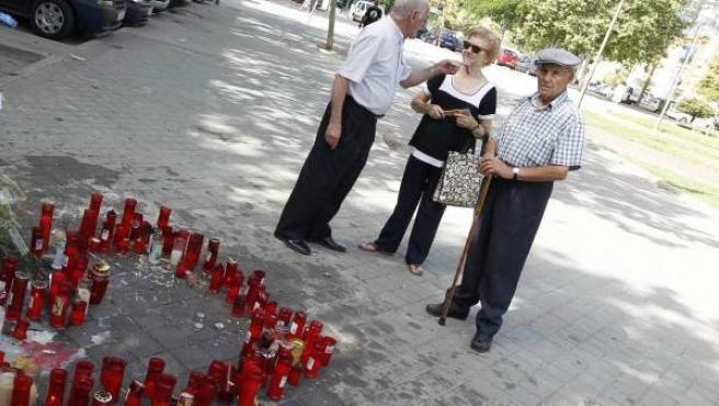 Varios vecinos se detienen frente al improvisado altar que recuerda en Vallecas el asesinato del joven Ramiro, de 20 años