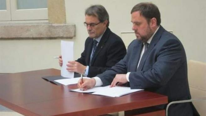 El presidente de la Generalitat en funciones, Artur Mas, y el líder de ERC, Oriol Junqueras, firmando el pacto.