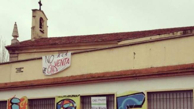 Pancarta de protesta sobre el encierro contra el cierre de los CAD en la fachada de la 'parroquia roja' de Entrevías.
