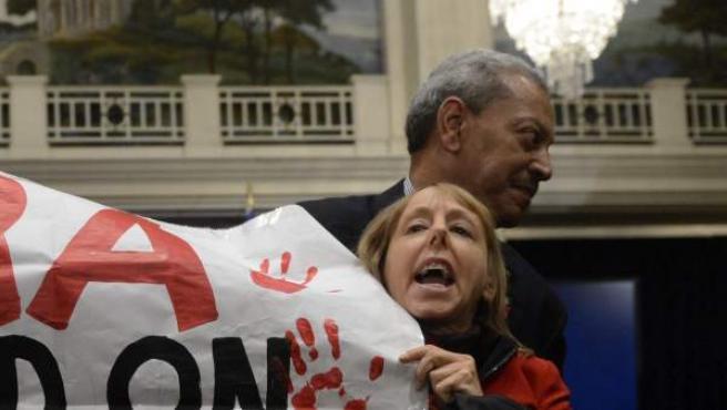 Una mujer es retirada de la sala por un agente de seguridad después de interrumpir la comparecencia ante la prensa del vicepresidente ejecutivo de la Asociación Nacional del Rifle (NRA) de EE.UU., Wayne LaPierre.