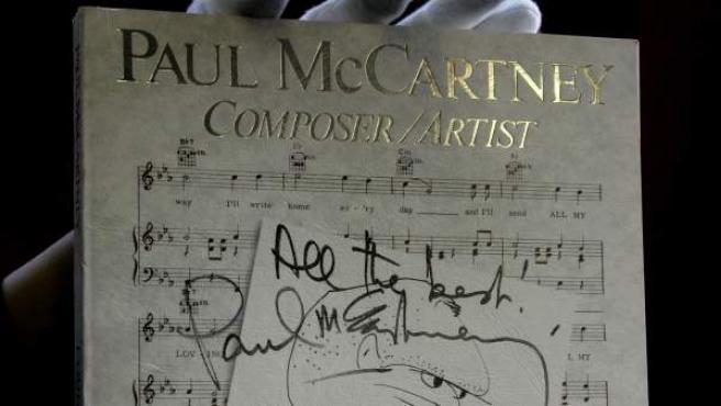 El autógrafo de Paul McCartney, en un libro sobre su vida subastado en Londres.
