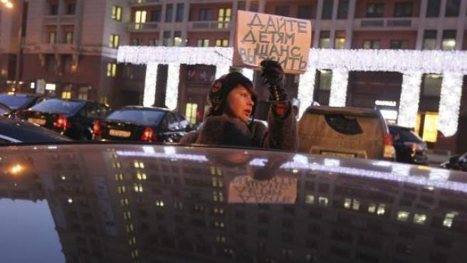 """Una manifestante sujeta una pancarta en la que se puede leer en ruso """"Dar a los niños una oportunidad para sobrevivir"""" durante una protesta frente a la Duma en Moscú."""