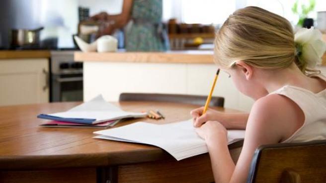 Una niña hace los deberes en su casa.