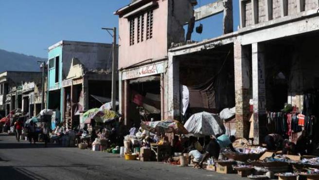 Varias personas caminan cerca de las ruinas de los locales comerciales de la avenida Desallines, en Puerto Príncipe (Haití).