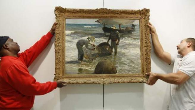 Dos operarios cuelgan en la pared el cuadro Pescadores valencianos, de Joaquín Sorolla, que la casa Sotheby's ha presentado en Madrid y que subastará en Londres junto a otras obras de pintores españoles.
