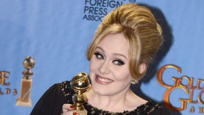 Adele muestra su premio a la mejor canción original en los Globos de Oro.