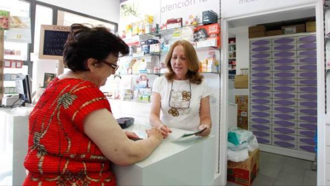 Una mujer consulta con una farmacéutica los detalles de una receta.