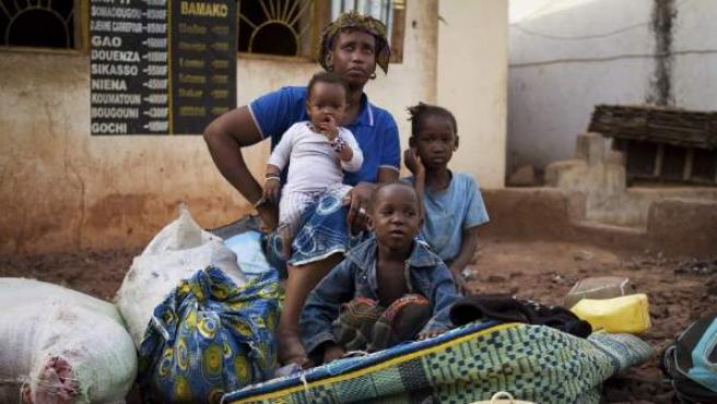 Una familia malí mientras espera en una parada de autobuses de Bamako.