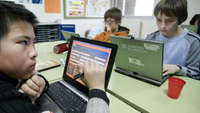 Unos niños utilizan ordenadores portátiles en el aula.