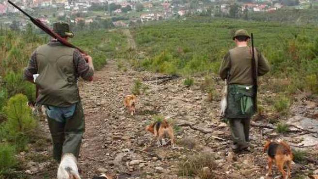 Cazadores con sus armas y sus perros.