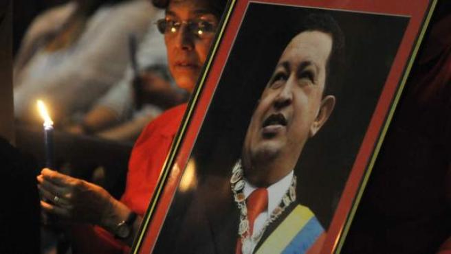 Una mujer, sentada cerca a una fotografía del presidente de Venezuela, Hugo Chávez, asiste el sábado 12 de enero de 2013, a una misa en la catedral de La Habana (Cuba) por la salud del gobernante. A la misa acudieron unas 300 personas, entre ellas estudiantes venezolanos y pacientes de ese país que se tratan en Cuba.