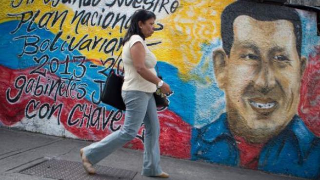 Una mujer camina frente a una pared con mensajes en apoyo al presidente venezolano Hugo Chávez, en Caracas (Venezuela).