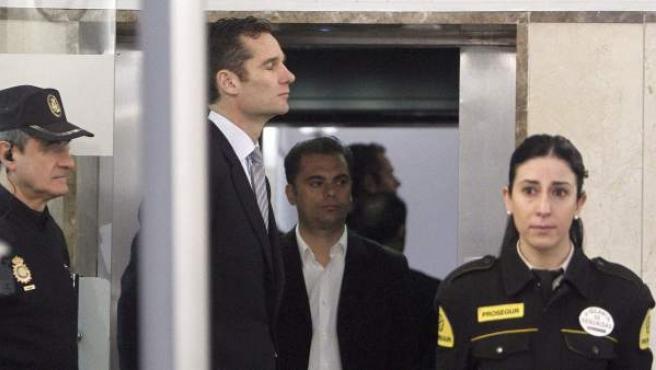 El duque de Palma, Iñaki Urdangarin (2-i), custodiado a la entrada a los juzgados de Palma.