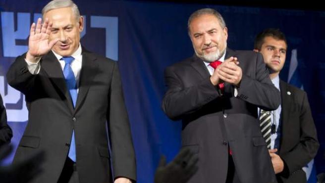 El primer ministro israelí, Benjamín Netanyahu (2i), saluda, cerca de su aliado político Avigdor Lieberman, después de dar su discurso de victoria, en Tel Aviv (Israel).