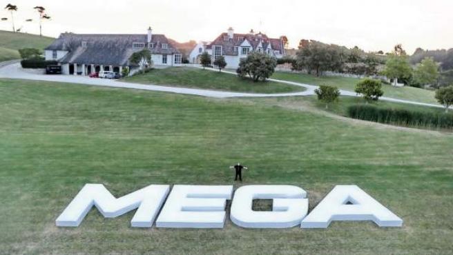 Kim Dotcom junto a un logo gigante de Mega.