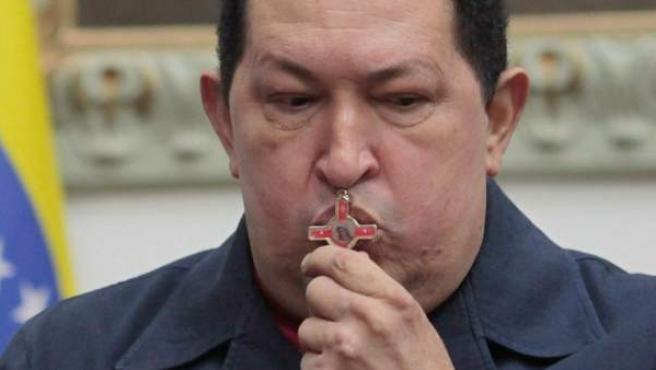 El presidente de Venezuela, Hugo Chávez, besa un crucifijo durante su anuncio en Caracas de la reaparición del cáncer.