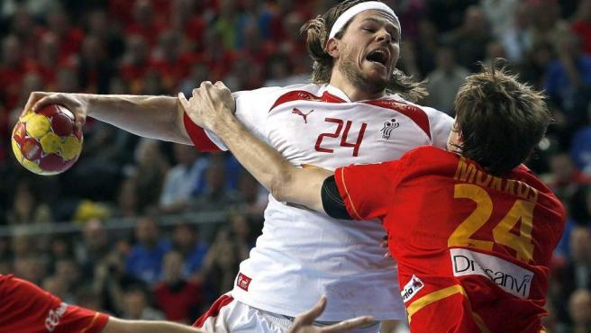 El jugador danés de balonmano, Mikkel Hansen, intenta disparar ante la oposición del español Viran Morros.