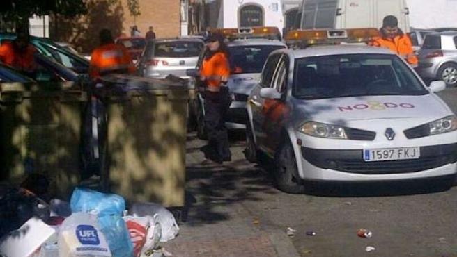 Miembros de Protección Civil junto a los contenedores de basura.