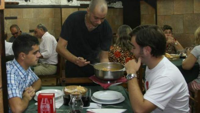 Un camarero sirve el menú del día a dos comensales.