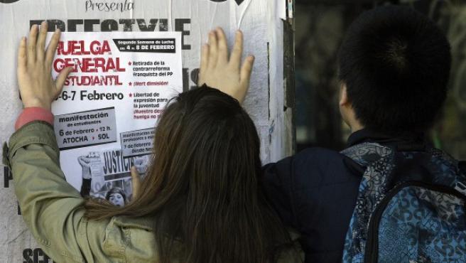 Miembros de un piquete del Sindicato de Estudiantes coloca en el Instituto Mariano José de Larra un folleto informativo sobre la huelga.