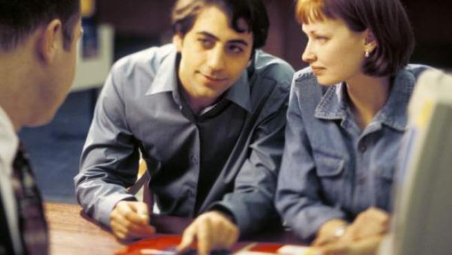 Una pareja informándose sobre las condiciones de una hipoteca.