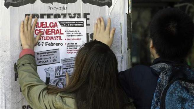Miembros del Sindicato de Estudiantes colocan un folleto informativo sobre la huelga de alumnado.