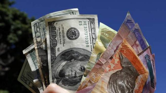 Billetes de dólar estadounidense y bolívares venezolanos.