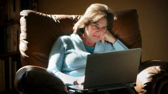 Una mujer navega por Internet en su portátil.