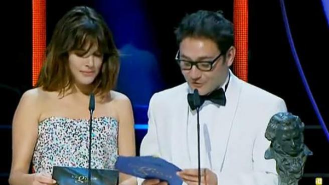 Adriana Ugarte sostiene la tarjeta auxiliar que pudo equivocarla, mientras que Carlos Santos tiene el sobre con el nombre del premiado.