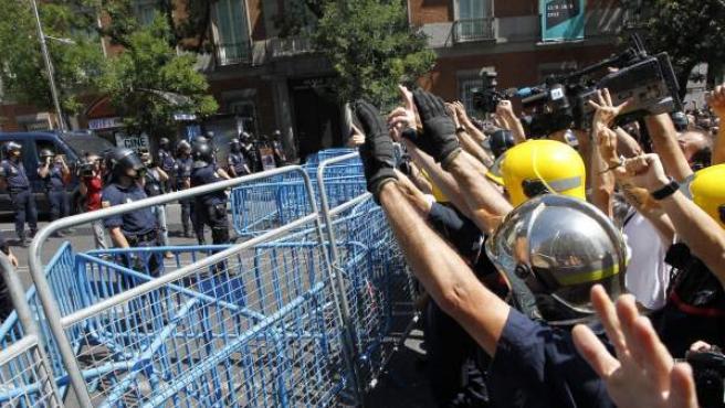 Un grupo de bomberos de Madrid levanta las manos frente a los agentes antidisturbios durante una manifestación de los funcionarios contra los recortes aprobados por el Gobierno de Mariano Rajoy.