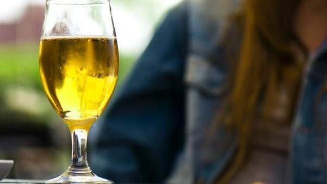 Una mujer tomando una cerveza en una terraza.
