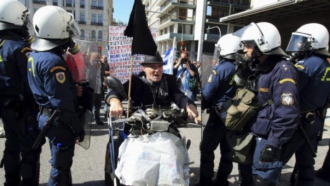 Un manifestante conduce su moto entre agentes de policía antidisturbios durante una manifestación frente al Parlamento griego.