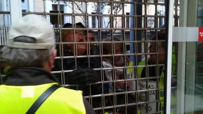 Dos mujeres del colectivo Yayoflautas gritan a través de la verja desde el interior de la Consejería de Sanidad.