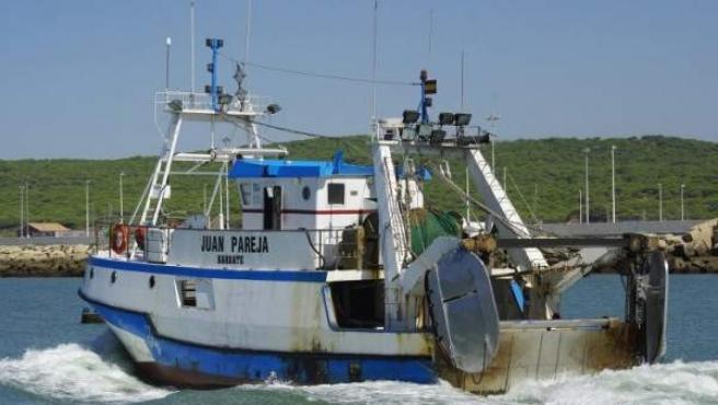 Un barco pesquero entrando al puerto del pueblo gaditano de Barbate.