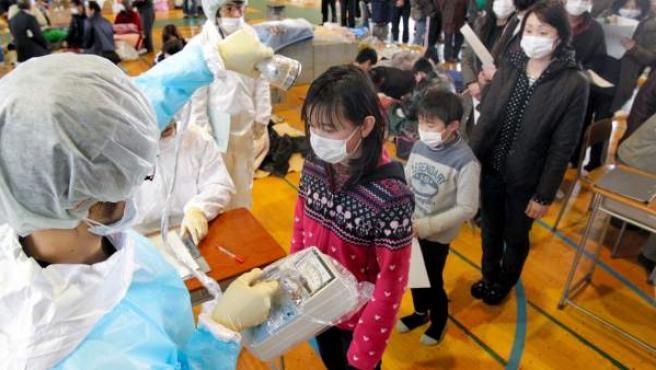 Personal médico mide la radiación en los residentes de Fukushima, en una imagen de archivo de marzo de 2011.