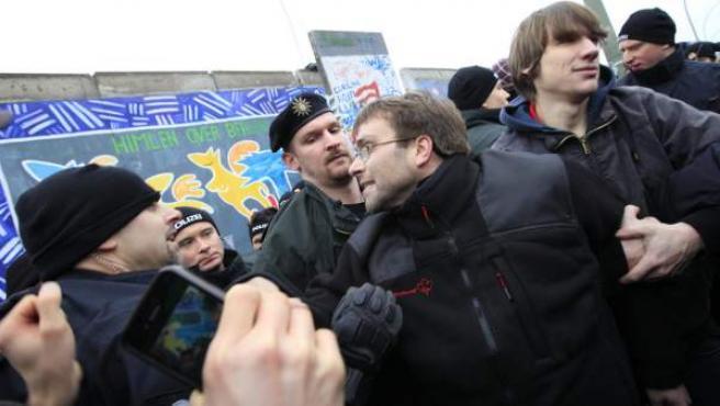 Manifestantes protestan mientras desmantelan una sección del muro de Berlín en Alemania, este viernes.