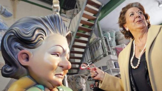La alcaldesa de Valencia, Rita Barberá, bromea ante un ninot que la representa vestida de barrendera durante la visita que ha realizado este martes a los talleres de los artistas falleros.