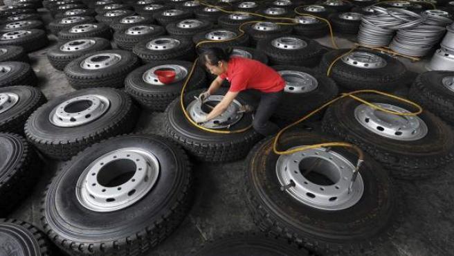 Un empleado infla unos neumáticos después de que sus compañeros encajaran las llantas, en una fábrica en Hefe, China.