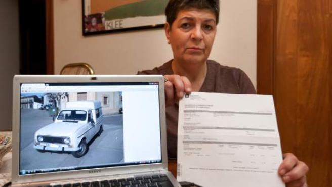 Andrea Cobo, de 61 años, con el impuesto que reclaman a su madre y el coche, un Renault 4L.
