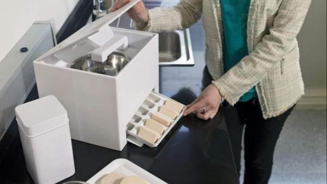 La joven emprendedora argentina Analía Blanco posa junto a la 'Fábrica de Jabón', el prototipo que ha patentado de un pequeño electrodoméstico que permite transformar el aceite usado en jabón biodegradable.