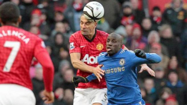 Rio Ferdinand y Demba Ba saltan para rematar un balón en el Chelsea - United.