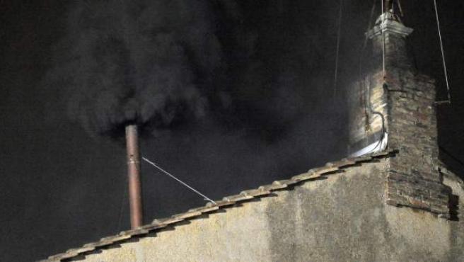 """Imagen de la chimenea de cobre sobre la capilla Sixtina desde donde se pueden ver la """"fumata negra"""" en la plaza de San Pedro, en Ciudad del Vaticano."""