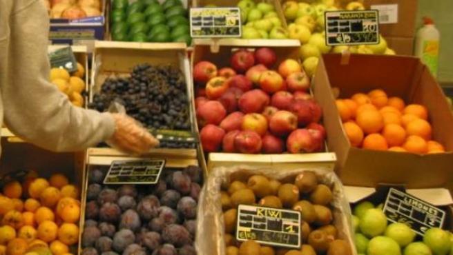 Una mujer compra fruta en un mercado.
