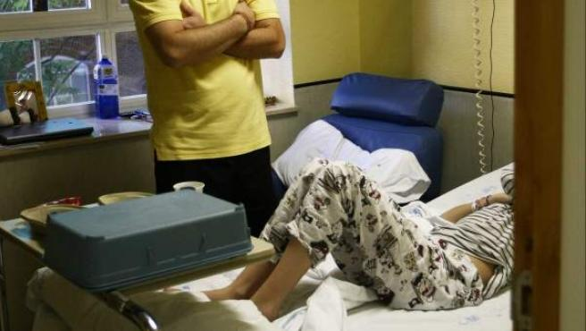 Un padre junto a su hija hospitalizada.