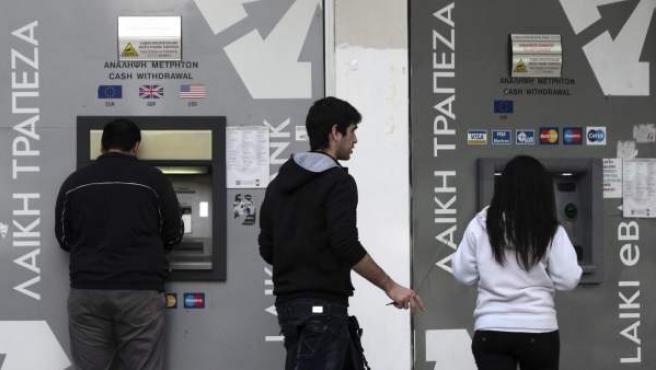 Varias personas sacan dinero de un cajero de Nicosia.