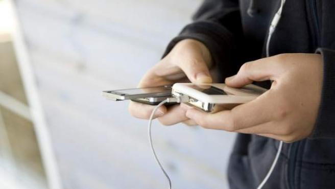 Un joven sostiene un reproductor de MP3.