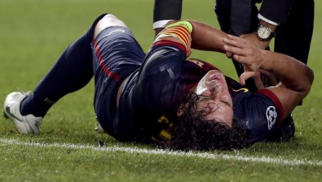 Carles Puyol atendido por los servicios médicos del Barça tras sufrir una luxación en el codo en el partido ante el Benfica.
